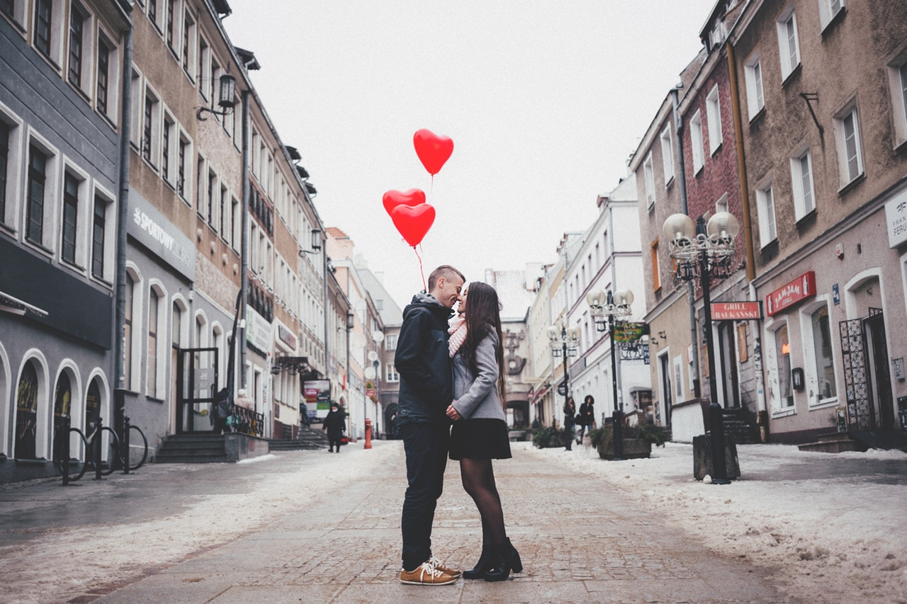 Young man and women on romantic walk with Valentine's Day balloons